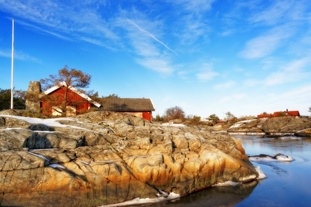 ice floes: Skagerrak coastline. Norwegian landscape. Red summer wooden cottage for guests. Around the undulating rocky coastline. Snow on the rocks. Frozen water. Broken ice floes. Blue sky over everything. Editorial