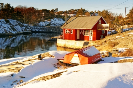 Traditional seasonal house used by fishermen, Red rorbu the rocky coast, curled around the rocks covered with snow. Wavy rocks covered with snow. In the background of the North Sea. Blue sky. Winter in Telemark municipality. Region of southeastern Norway.