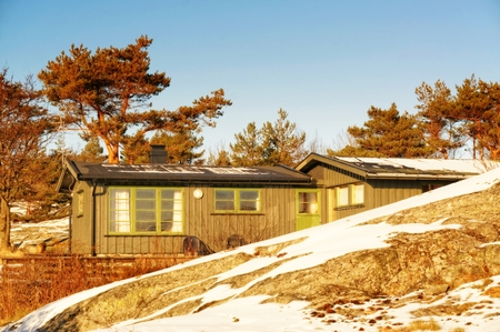 Surrounding trees in winter robe, without leaves. Among them, the green cottage hidden among the rocks in winter. On the rocks undulating layer of snow. Blue sky. Winter in Telemark municipality. Region of southeastern Norway. North Sea Coast. Skagerrak c