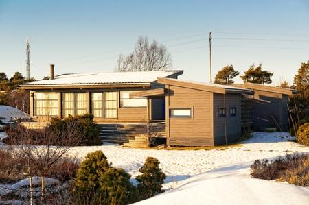 Norwegian coast vegetation surrounds the gray cottage with a big green terrace. Around the spruces, pines, heathers in the winter coat. North Sea Coast. Skagerrak coastline. Norwegian winter landscape.