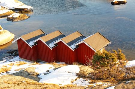 quadruple: Red wooden rorbu quadruple over the North Sea water. Norwegian vegetation on the coast. Around the spruces, pines, heathers in the winter coat. North Sea Coast. Skagerrak coastline. Norwegian winter landscape.
