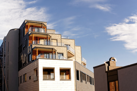 decorative balconies: Arendal, Aust-Agder. Norway - February 2015.  Modern brick building, large glass windows. Walls covered with decorative plates. The rooftop sun decks and balconies