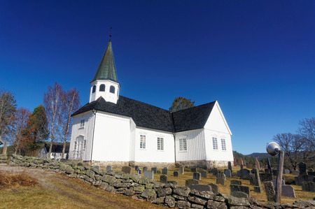 cemetry: Drangedal, Norway, March 21, 2015: Whitewashed Norwegian wooden church  with square tower surrounded by graves with similar headstones and between them manicured lawn. Early spring.