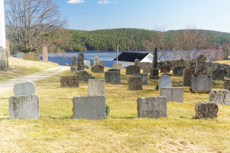cemetry: Drangedal, Norway, March 21, 2015: Cemetry situated by lake Tokevann. Square tower surrounded by graves with similar headstones and between them manicured lawn. Early spring.