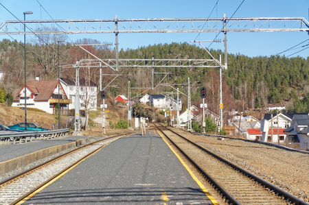thorium: Drangedal, Norway, March 21, 2015: Railway Tracks and asphalt railway platform in a small town.. Early spring.