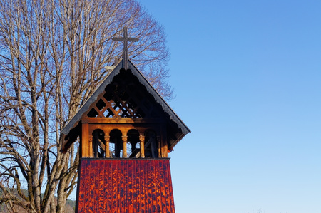 cemetry: Heddal, Norway, March 21, 2015: Old traditional temple bell tower of the temple wooden sloping roof of the old temple, a small cross on roof. Early spring. Stock Photo