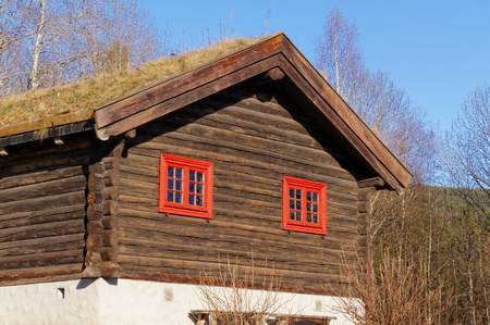 red shutters: Notodden, Norway, March 21, 2015: Open Air Museum Traditional Norwegian old authentic farm. The building of round logs, small red shutters. Thick green glass in the windows. Early spring. Editorial