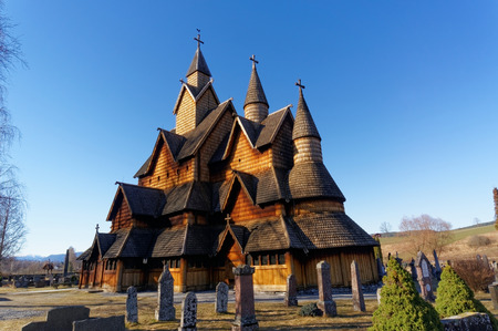 cemetry: Heddal, Norway - March 21, 2015: Old church building surrounded by tombstones. Wooden church  with triple nave stave church. Surrounded by graves with similar headstones. Early spring. Editorial