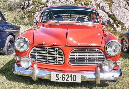 islanders: Froya island, Norway - 24 July 2016: Front of the classic Volvo car in red  at cars show in norwegian Islanders Classic Car Club - Kysttreffet 2016.  Island in the Atlantic Ocean and Norwegian fjord.