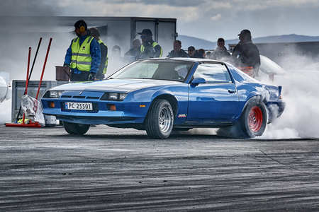 Froya, Norway, 24 June 2016: Norwegian high-skill motor sport  competitions and demonstration of fast cars drifting in Norway. Fuming blue car racing. Cars drifting, burning out, sliding, cars driving fast. Island in the Atlantic Ocean and Norwegian fjord Editorial