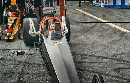 ocea: Froya, Norway, 24 June 2016: Norwegian high-skill motor sport  competitions and demonstration of fast cars drifting in Norway. Woman driver in a black race car front view. Cars drifting, burning out, sliding, cars driving fast. Island in the Atlantic Ocea
