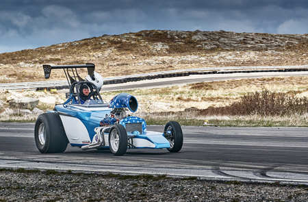 drifting: Froya, Norway, 24 June 2016: Norwegian high-skill motor sport  competitions and demonstration of fast cars drifting in Norway. White blue racing car with a driver. Cars drifting, burning out, sliding, cars driving fast. Island in the Atlantic Ocean and No