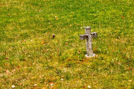 headstones: Cross in the grass. Autumn in the Norwegian cemetery Vegetation autumn. Autumn colors. Rock disc headstones.