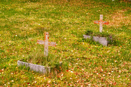 headstones: Two graves in autumn. Autumn colors. Rock disc headstones. An island in the Norwegian Sea. Stock Photo