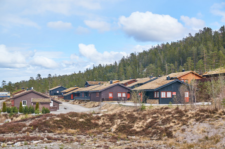 Gautefall, Norway - May 2, 2015:  Brown, black wooden residential houses. Green roof. Early spring, around the coniferous forest Gautefall is a village in Drangedal municipality, Norway.