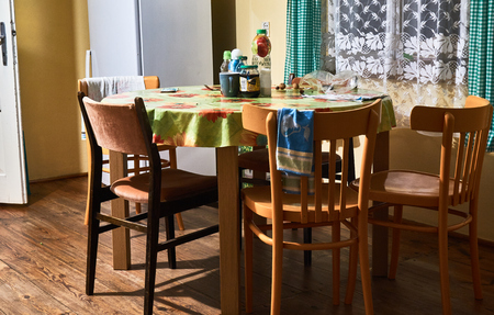 stove pipe: Lubaczow, Poland - August 17, 2016:  Dining room decorated in the old style. Wooden planks on the floor. Round table. Old chairs pipes on the walls. Old dishes.