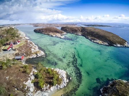 Daloya, Norway - April 14, 2017: Colorful sky, a small Norwegian island.Blue water. Bay on a small island Aerial view from flying drone.