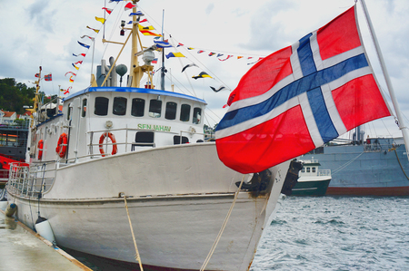 Kragero, Norway - August 9, 2014: Traditional wooden boat, boat festival. Maritime haven in the city of Norway Telemark. Colorful flags. Norwegian summer.