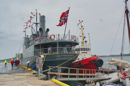 battleship: Kragero, Norway - August 9, 2014: Boat festival. DS Hestmanden Norwegian steam, driven cargo ship with passenger capacity, reaching a museum ship and a war memorial to the war sailors.