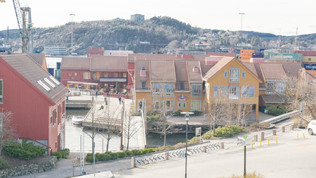 Kristiansand, Norway - June 4, 2015: Top view on colorful buildings, red, canvas and orange wooden business buildings and restaurants on the harbors harbor. Gulf of Kristiansand.