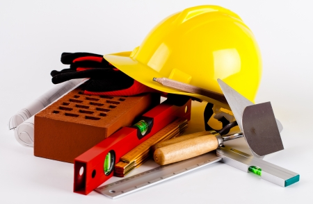 brick, yellow hard hat, tools and construction plans photo