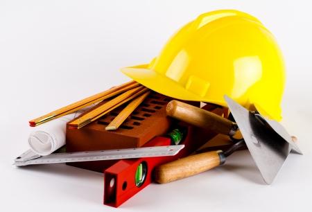 baksteen, gele helm, gereedschappen en bouwplannen