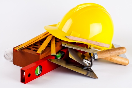 protection plan:  brick, yellow hard hat, tools and construction plans