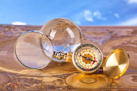 crystal globe compass and old map