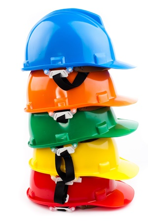 building safety: colorful safety hardhats isolated on white