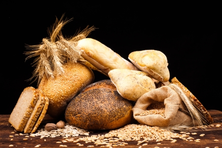 assortment of baked bread on wood table and black background