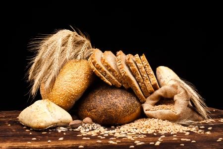 surtido de pan horneado en la mesa de madera y fondo negro