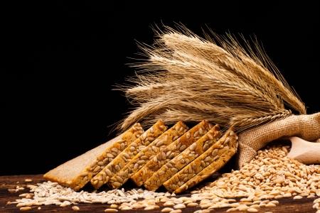 Assortimento di pane cotto sul tavolo in legno e sfondo nero Archivio Fotografico - 16697162