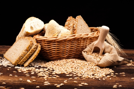 assortment of baked bread on wood table and black background photo