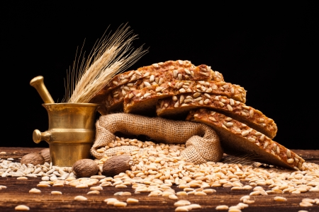 assortment of baked bread on wooden table and black background photo