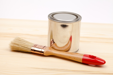 Cans of paint with paintbrush isolated on white photo