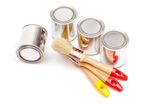 Cans of paint with paintbrushes isolated on white photo