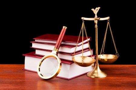 arbitrar: libros de la justicia, la escala y lupa Foto de archivo