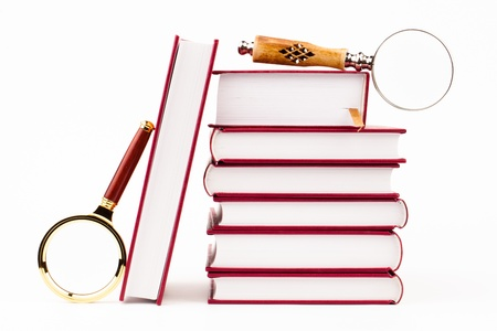 magnifying glass and pile of books isolated on white Stock Photo - 18472441
