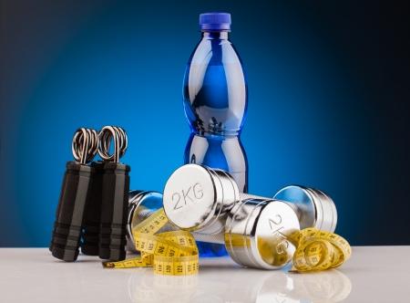 botella de plastico: mancuernas de fitness y una botella de agua
