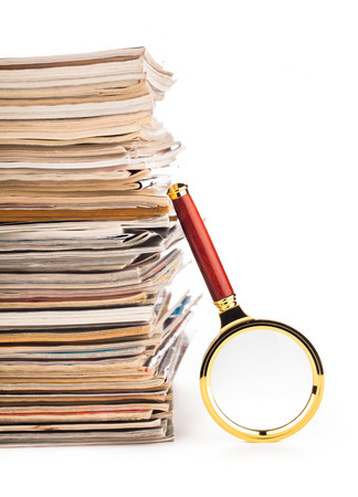pile of newspapers and magnifying glass  photo