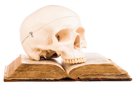 old book and human skull isolated on white  photo