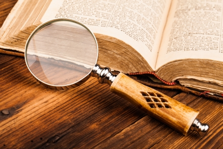 law library: old book and magnifying glass