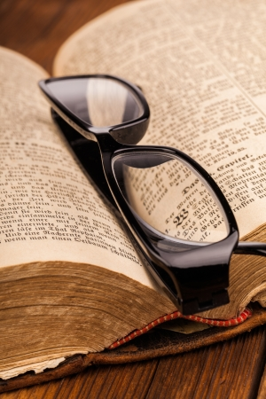 old book and reading glasses photo