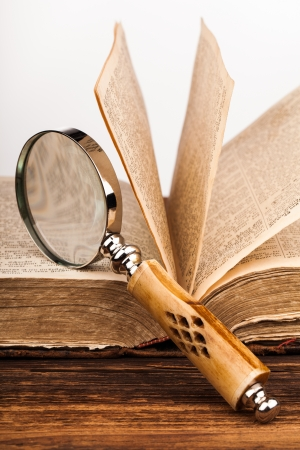 old book and magnifying glass photo