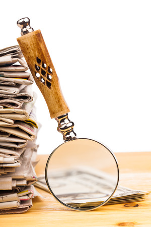 magnifying glass and pile of newspapers  photo