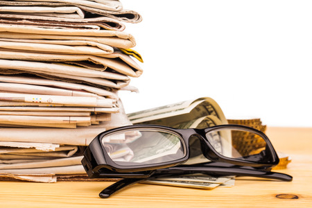 broadside: reading glasses pile of newspapers and money