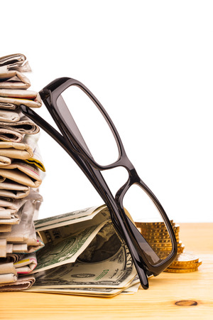 reading glasses pile of newspapers and money photo