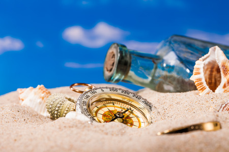 spiral: bottle and compass on sand and blue sky Background Stock Photo