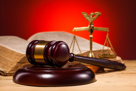judge gavel scales and old book on wooden table Stock Photo