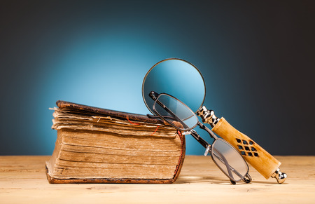 book magnifying glass  and glasses on wooden table and blue background photo